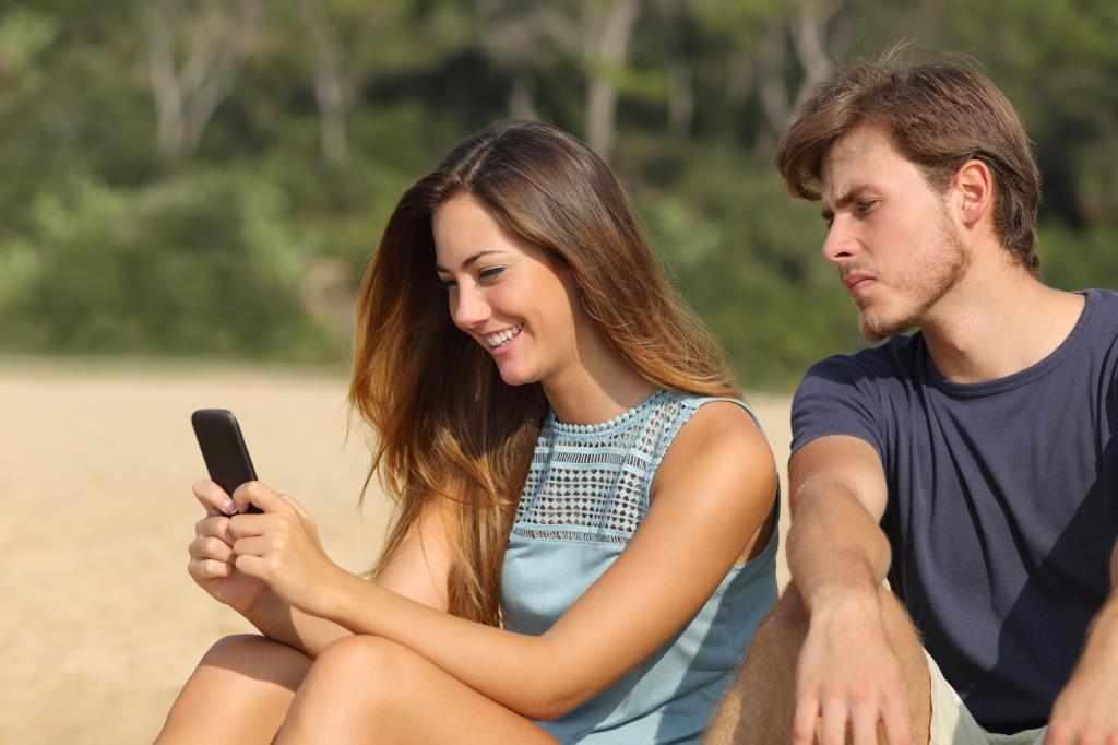 Парень заглядывает в телефон девушки
